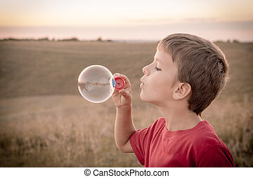 Boy blowing up the soap bubbles - boy blowing up the soap...