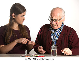 young woman helps senior man to take his pills and water in...