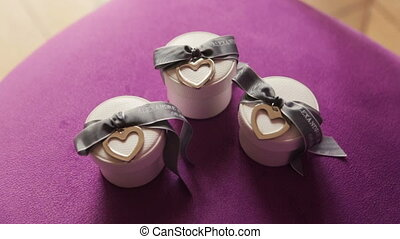 Boxes with wedding rings on purple background