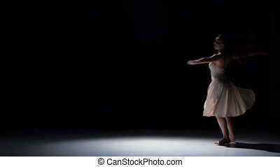 Young woman dancer dancing contemporary dance, jumping and doing a split, on black, shadow
