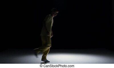 Breakdance dancer in yellow suit dance on black, shadow