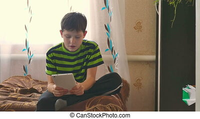 boy and tablet - boy tablet playing game browsing internet...