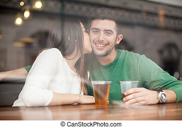 Young man drinking beer with his girlfriend - Portrait of a...