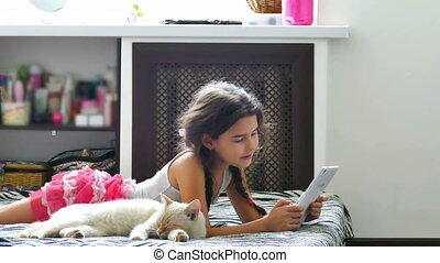 girl and tablet - Teenage girl stroking a cat plays tablet