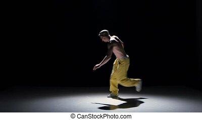 Breakdance dancer starts dance, on black, shadow