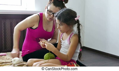 Mother and daughter knitting - woman and a teen lifestyle...