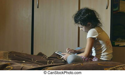 girl reading book - girl with browsing tablet in room...