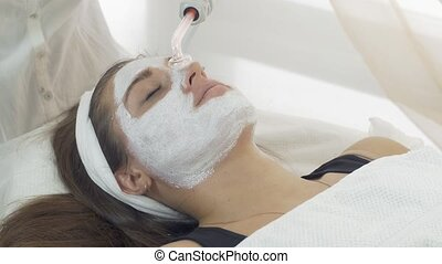 Close up darsonvalization face of girl with mask in saloon. Cosmetic procedure