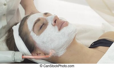 Close up darsonvalization girl face with mask in saloon. Cosmetic procedure