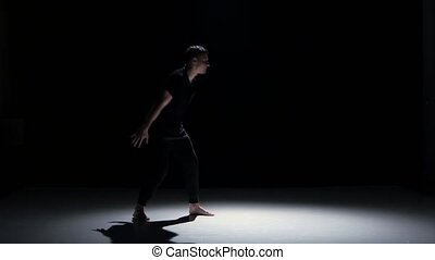 Contemporary dance moves of three dancers on black, shadow