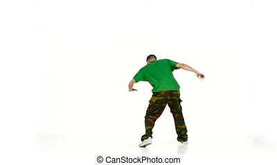 Talanted young dancer man in green shirt dancing breakdance...
