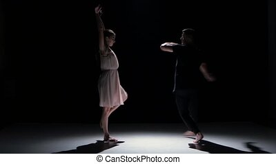 Man and woman performing a contemporary dance on black, shadow