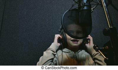 girl sings in the music studio - teen girl in headphones...