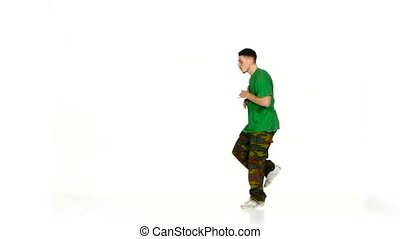 Talanted young dancer man in green shirt dance breakdance on...