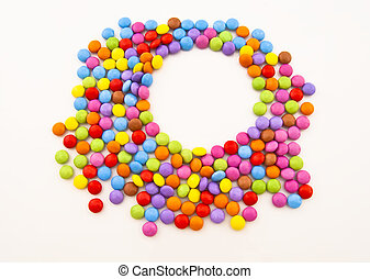 Multi-coloured chocolate candy on a white background and a...