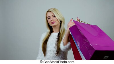 Young woman holds shopping packages, looks into one of them,...