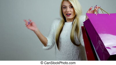 Young blonde female model makes expressions of excitement with shopping colorful packages in her hands.