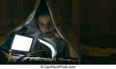girl reading book - girl reading book under covers with...