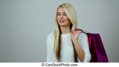 Fashion girl calls by cell phone and holds a bunch of shopping packages; footage in studio.