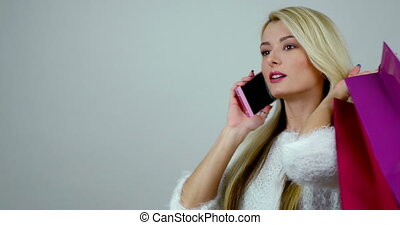 Portrait of a young excited blonde woman talks on cell phone...