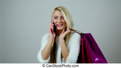 Funny fashion girl answers to a call on her mobile device and holds shopping packages in her hands.