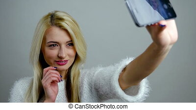 Fashion girl, blonde makes poses for a selfie on her mobile device.