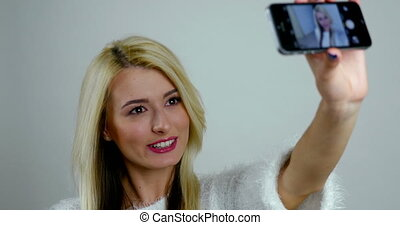 Young woman takes selfie pictures on smartphone's camera.