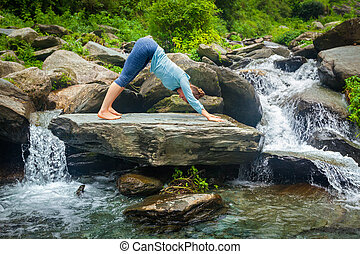 Woman doing yoga oudoors at tropical waterfall - Young...