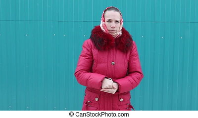 woman in a red jacket sneezes