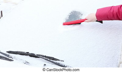 woman to clear snow from the car window.