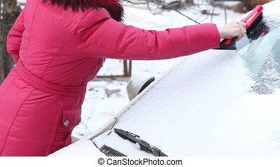 woman to clear snow from the car window - woman in a red...