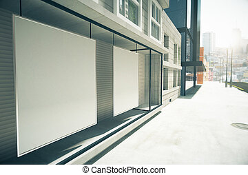 Blank posters in the window on the first floor of building,...