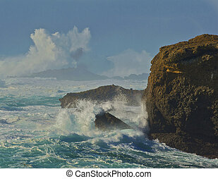 Large waves explode as they hit the large rocks near the...
