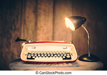 Vintage typewriter with lamp on wooden table at wooden wall...