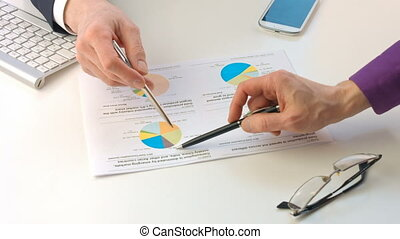 Male hands pointing at paper containing data about economic...