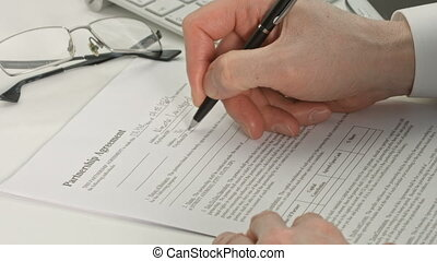Hand of businessman in suit filling partnership agreement -...