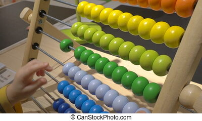 little boy counts on abacus