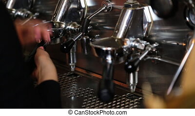 Close up of hands of young waitress preparing coffee in...