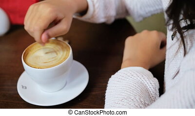 Lady in a white pulloverholding a teaspoon and stirring prepared hot delicious  coffee with milk in a white cupat coffee shop.