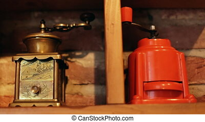 Antique vintage manual coffee grinders on a bricky...