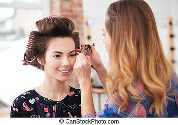 Visagist doing professional makeup to model with curlers in...