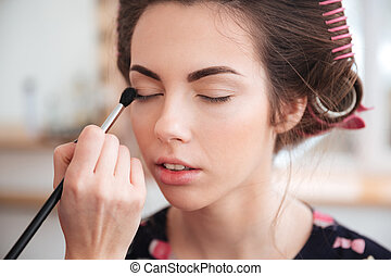 Makeup artist applying eyeshadow with brush to young woman -...