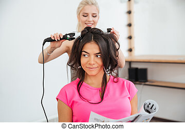 Woman hairdresser making hairdo using curling iron in beauty...