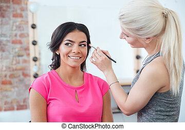 Female makeup artist applying professional brush for eyes of...