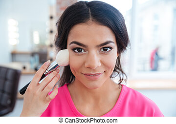 Female visagist with brush doing professional makeup to...