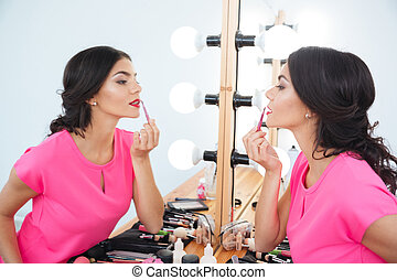 Beautiful woman standing near mirror and putting on red...