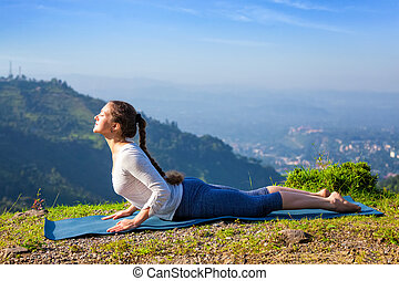 Woman practices yoga asana bhujangasana cobra pose -...