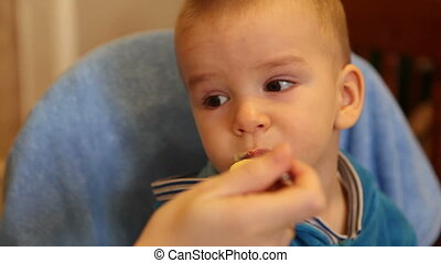 Mom feeds the baby porridge from a spoon HD