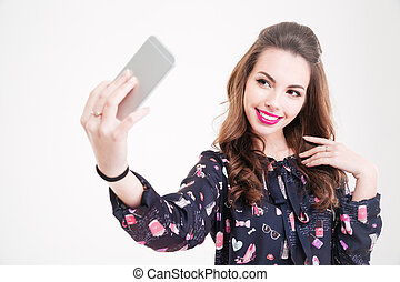 Cheerful charming young woman making selfie using smartphone...