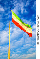 Iran flag against blue sky in Tehran